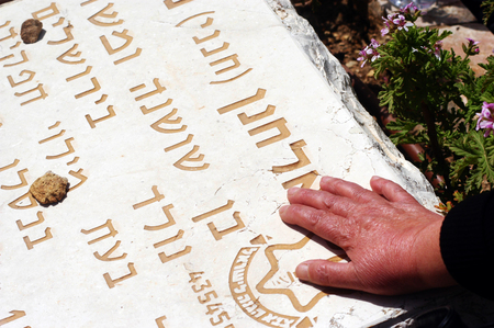 middle east fighting: JERUSALEM - APRIL 23:A relative of a fallen soldier puts a hand on the grave of the victim at a ceremony to mark Memorial Day or Yom Hazikaron at the Memorial Service for Victims of Terror on Mount Herzl in Jerusalem Monday, April 23, 2007