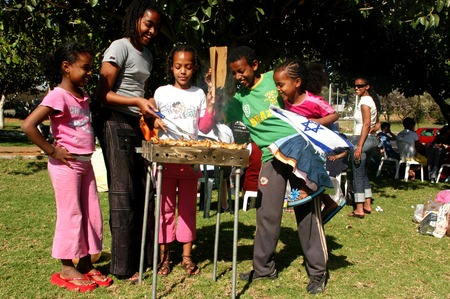 photojournalism: KERYAT GAT MAY 03:Ethiopian children celebrating the israeli independence day by having a BBQ in Kiryat Gat on Wednesday May 03, 2006.