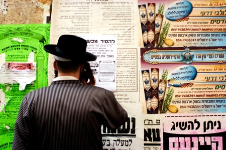 israelis: JERUSALEM - OCT 14:Orthodox Jewish man reads street signs in Mea Shearim on October 14 2005 Jerusalem, Israel.Its one of the oldest Jewish neighborhoods in Jerusalem populated mainly by Haredi Jews.