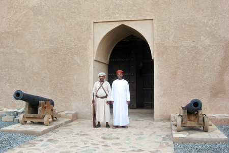 guia de turismo: RUSTAQ - DEC 23: Omani guard and a tour guide at the gate to Al Hazm Fort on December 23 2007 near Rustaq, Oman.Its an outstanding example of Omani Islamic architecture and was built in 1711 AD.