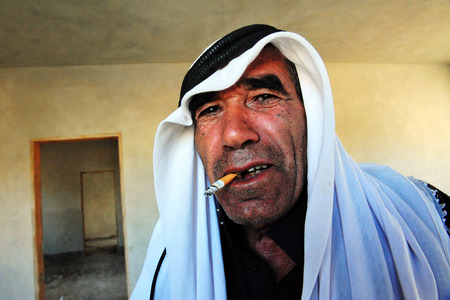 nomadic: WESTERN NEGEV - NOVEMBER 26:A portrait of a Bedouin man from Lakyia Bedouin village in southern Israel wearing a traditional kufeya smokes a cigarette on November 26 2008.egev Bedouin are formerly nomadic and later also semi-nomadic Arabs who live by rear Editorial