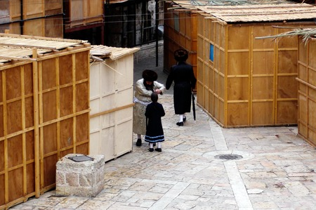 succos: JERUSALEM - OCT 20:Orthodox Jewish people outside Sukkah booths during Sukkot  Jewish holiday in Mea Shearim on October 20 2005 Jerusalem, Israel.