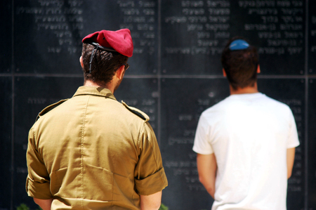 JERUSALEM - APRIL 23: Israeli paratrooper and youth reads the names of fallen soldiers during the Memorial Day or Yom Hazikaron at the Memorial Service on Mount Herzl in Jerusalem in April 23, 2007.
