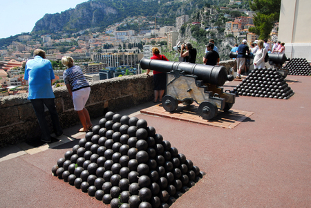 french ethnicity: MONACO - MAY 07:Visitors stand beside old canons near the Princes Palace of Monacoa on May 07 2008.Its the official residence of the Prince of Monaco, built in 1191.