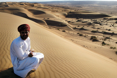 skull cap: WAHIBA DESERT - DEC 29 2007: Omani man sit on a sand dune over looking the desert landscape of the Wahiba Sands Desert, Oman.In summer, air temperatures  can rise to 50 Celsius 122 Fahrenheit