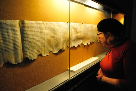 QUMRAN, ISR - DEC 14:Woman looks at the Dead Sea Scrolls on display at the caves of Qumran on December 14 2008.The Dead Sea Scrolls were discovered in eleven caves in Qumran near the Dead Sea between the years 1947 and 1956.