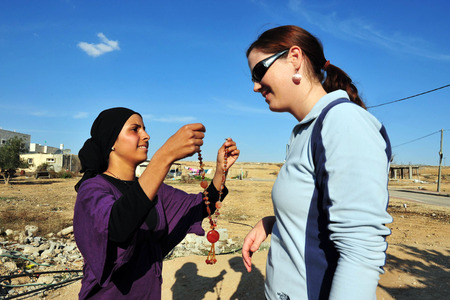 bedouin: WESTERN NEGEV - NOVEMBER 26: A Bedouin woman from Lakyia Bedouin village in southern Israel gives a necklace to a visiting tourist as a welcome gift on November 26 2008.egev Bedouin are formerly nomadic and later also semi-nomadic Arabs who live by rearin