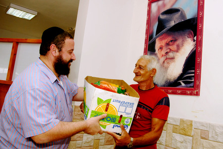 SDEROT - SEPTEMBER 05:Member of Chabad Organization is giving food to poor Jewish families during the jewish holidays on September 05 2007 in Sderot,Israel. Editorial
