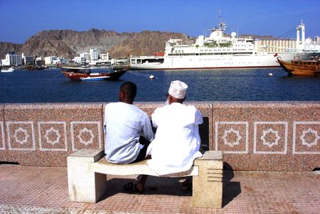 muttrah: MUTTRAH, OMAN - DEC 22 2007:Omani people looks at ship and traditional Omani sails boat mooring at Port Sultan Qaboos in Muscat, Oman. Muscat is on of the worlds largest natural harbors.