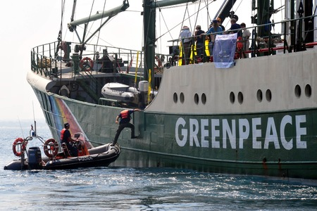 greenpeace: ASHKELON, ISR - SEP 03:Israeli water police officer climbing on the Rainbow Warrior on Sep 08 2008, during protest against Israels plan to build a new electric power plant fueled by coal.