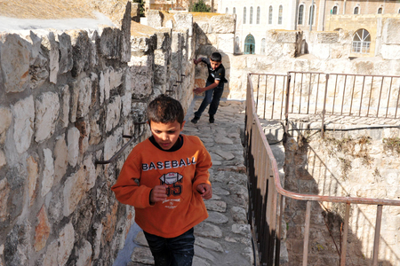 ottoman empire: JERUSALEM - NOV 05:Arab boys runs on Jerusalem old city walls on November 05 2010.The walls were built between the years 15351538, during the reign of the Ottoman empire by Sultan Suleiman the Magnificent.
