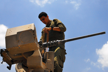 automatically: NIRIM, ISR - JUNE 11:Israeli fighter loading Machine Gun on June 11 2008.Its a belt-fed weapons repeating firearms that when triggered it load and fire automatically until ammunition is exhausted. Editorial