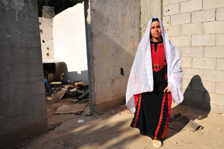 bedouin: WESTERN NEGEV - NOVEMBER 26:Bedouin girl  traditionally dressed with a burqas in a Lakyia Bedouin village in southern Israel.egev Bedouin are formerly nomadic and later also semi-nomadic Arabs who live by rearing livestock in the deserts of southern Israe