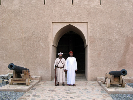 guia turistico: RUSTAQ - DEC 23: Omani guard and a tour guide at the gate to Al Hazm Fort on December 23 2007 near Rustaq, Oman.Its an outstanding example of Omani Islamic architecture and was built in 1711 AD.