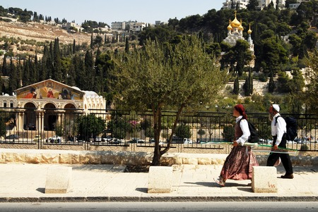 mideast: JERUSALEM - SEP 28:Jewish couple pass by Mount of Olives, Church of All Nations and Church of Mary Magdalene on September 28 2007 in Jerusalem ,Israel.The Mount of Olives is one of the most important holy sites for the three monotheistic religions  Editorial