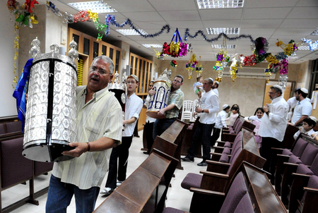 SDEROT - OCTOBER 21: Israeli Jewish men melebrate Simchat Torah by dancing with the scrolls of the Torah at a Synagogue on October 21 2008 in Sderot, Israel. Simchat Torah is a celebratory Jewish holiday that marks the completion of the annual Torah readi
