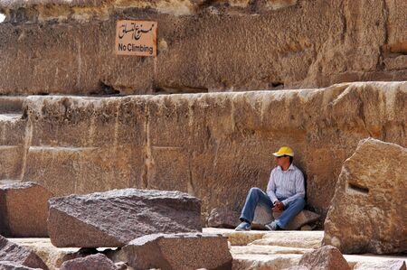 necropolis: Tourist sits under a sign reads: No Climbing at the great pyramids in Giza, Egypt.