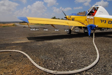 fueled: BEERI, ISR - MAR 26:An Israeli fertilizing plane being fueled on a runway on March 04 2008.Crop dusting with insecticides began in the 1920s in the United States. Editorial