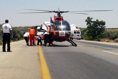 israel people: ASHKELON, ISR - JUNE 10:Israeli rescue helicopter evacuate injures after a deadly car accident on June 10 2008.The first air ambulance service originated in Australia during 1928.