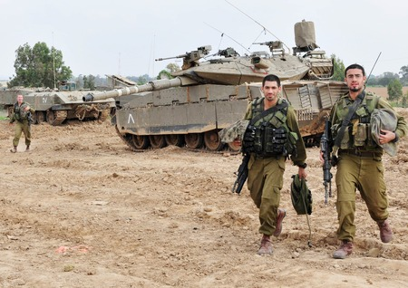 NACHAL OZ, ISR - NOV 12:Israeli soldiers near Merkava tank on NOV 12 2008.Its IDF battle tank designed for rapid repair of battle damage, survivability, cost-effectiveness and off-road performance. Editorial