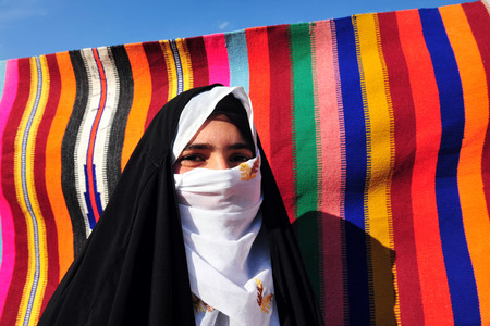 nomadic: WESTERN NEGEV - NOVEMBER 26:Bedouin girl  traditionally dressed with a burqas in a Lakyia Bedouin village in southern Israel.egev Bedouin are formerly nomadic and later also semi-nomadic Arabs who live by rearing livestock in the deserts of southern Israe