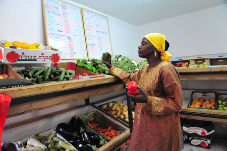 hebrews: DIMONA,ISR - NOV 06:Black Hebrews woman buy vegetables on Nov 3 2008.The group maintains a vegan diet as part in their belief in Gods promises to Adam in Genesis. Editorial