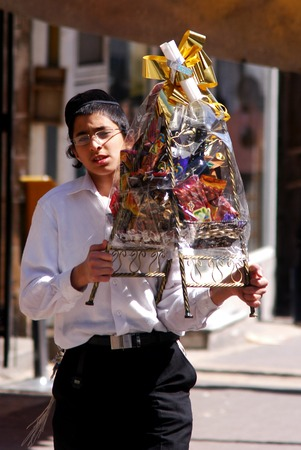 esther: JERUSALEM - MARCH 05: Ultra-orthodox Jewish young man carry Mishloach Manot Purim basket during the Jewish holiday Purim on March 05 2007 in Mea Shearim in Jerusalem, Israel.