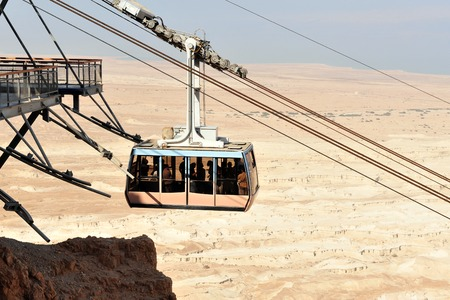 arava: MASADA,ISR - SEP 17:The cable car to Masada stronghold on September 17 2008 in Judea Desert, Israel.Masada considered as most popular tourist destination in Israel, outside of Jerusalem. Editorial