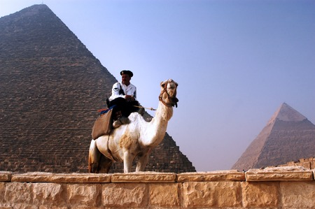 militant: GIZA - APRIL 27: Egyptian tourist police on a camel guards the Pyramid of Khufu at the great pyramids in Giza, Egypt on April 27 2007.Since the 90s tourist became a target by Muslim militant in Egypt Editorial