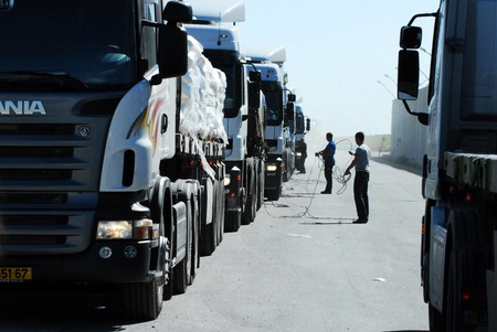 gaza: KEREM SHALOM, ISR - FEB 04: Line of cargo trucks in Kerem Shalom border crossing on Feb 04 2009. The crossing is used by trucks carrying goods from Israel to the Gaza Strip. In 2012, the rate of traffic was 250 trucks a day.
