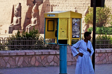 sharply: LUXOR - MAY 02:An Egyptian man stands near a payphone in Luxor, Egypt on May 02 2007.Payphone revenues have sharply declined in many places, largely due to the increased usage of mobile phones. Editorial
