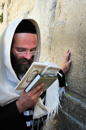 hassid: JERUSALEM  - JULY 28:Jewish Man wrapped in talit pray at the Western Wall on July 28 2009 in Jerusalem, Israel.Its the most sacred site by the Jewish faith outside of the Temple Mount itself.