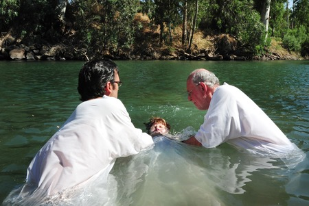 TIBERIAS - MAY 18:Christian pilgrims during mass baptism ceremony at the Jordan River in North Israel on May 18 2009.In Christian tradition, Jesus was baptised in the River Jordan by John the Baptist. Редакционное