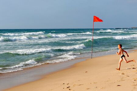 drowns: ASHDOD - JULY 23:Young man runs to sea on warning Red flag on July 23 2009.Every summer about 30 people drowns along Israel coast due to hostile sea condition of strong winds and underwater currents.