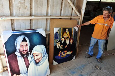 sephardic: NETIVOT, ISR - AUG 24:Jewish man holds oil paintings of Baba Sali on Aug 24 2009.Rabbi Yisrael Abuhatzeira was kabbalist who renowned for his alleged ability to work miracles through his prayers. Editorial