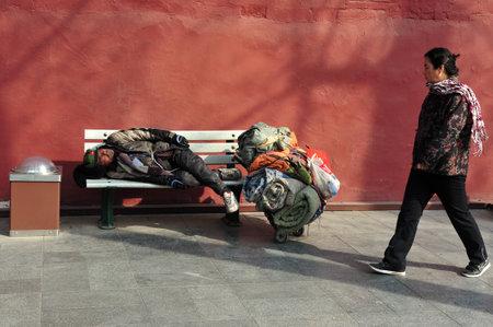 gente triste: BEIJING - 11 de marzo: sleeeping sin hogar chino fuera de los muros Ciudad Prohibida, el 11 de marzo de 2009 en Pekín, China.More de 135 millones de personas en China viven con menos de 1 dólar al día