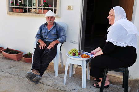 MAJDAL SHAMS - AUGUST 23:A Druze  husband and wife sit outside their front door in Majdal Shams,Israel on August 23 2009.The number of Druze people worldwide exceeds one million, with the vast majority residing in the Middle East.