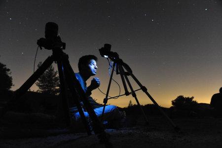 anochecer: Kiryat Gat - 12 de agosto: Hombre que mira hacia fuera al cielo nocturno y fotografiar las estrellas con sus cámaras en un trípodes el 12 de agosto 2009, cerca de Kiryat Gat, Israel.It de es un nombre común para el camino visible de un meteorito, ya que entra en la atmósfera para convertirse am