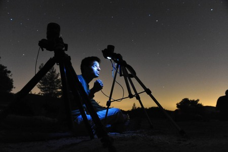 gat: KIRYAT GAT - AUGUST 12: Man gazing out at the night sky and photographing the stars with his cameras on a tripods on August 12 2009 near Kiryat Gat, Israel.Its is a common name for the visible path of a meteoroid as it enters the atmosphere to become a m