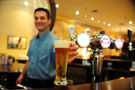 beer pump: ASHKELON - JULY 27:Bartender pours a glass of beer on July 27 2009 in Ashkelon, Israel.Beer is the oldest alchoholic beverage and has been around since at least the ancient Sumerians of 2600 B.C Editorial