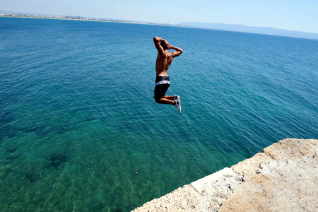 akko: Arab boy jumps from the top of the ancient walls Acre Akko, Israel. Editorial