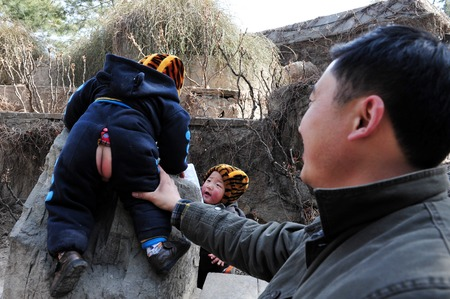 one child: BEIJING - MARCH 13:Chinese twins and their father at the  Summer Palace on March 13 2009 in Beijing,China.When One Child Policy was adopted in 1979,Chinas population was about 972 million. Today its about 1.343 billion people.