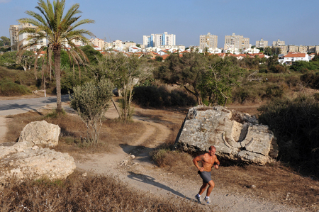 encompasses: ASHKELON, ISR - JULY 23:Israeli man runs in Ashkelon National Park on July 23 2009.Ashkelon National Park, on the southern Mediterranean coast, encompasses history and heritage thousands of years old.