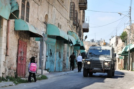 middle east conflict: HEBRON, ISRAEL - SEP 08:Israeli IDF Jeep pass by arab people in Hebron on September 09 2009.There are 163,000 Palestinians living in Hebron Editorial