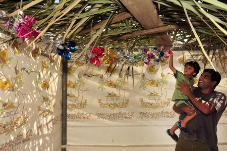 NETIVOT - OCTOBER 02: Israeli Jewish father and his son decorates their Sukkah on the eve of the Jewish holiday Sukkoth on October 02, 2009 in Netivot, Israel. Éditoriale