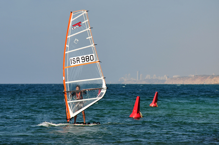 olympic sports: HERZLIYA,ISR- OCT 06:Israeli wind surfer surf along Herzliya Pituah skyline on Oct 06 2009.Windsurfing is one of Israels most successful olympic sports.