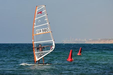olympic sports: HERZLIYA,ISR- OCT 06:Israeli wind surfer surf along Herzliya Pituah skyline on Oct 06 2009.Windsurfing is one of Israels most successful olympic sports.