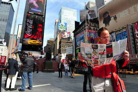 entertainment industry: NY - OCT 08:Tourist reads a brochure of Broadways shows in Time Square on October 08 2010 in Manhattan New York, USA.Its a major center of the worlds entertainment industry. Editorial