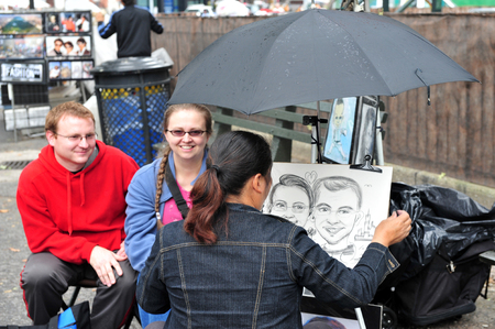 exaggerate: NY - OCT 09:Street artist draws caricature on October 09 2009 in Manhattan New York.The earliest caricatures ever discovered belong to Leonardo Da vinci from the 15th century