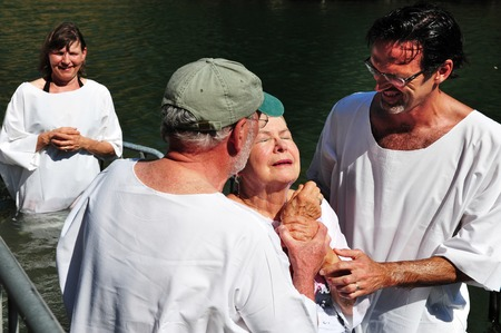 baptize: TIBERIAS - MAY 18:Christian pilgrims during mass baptism ceremony at the Jordan River in North Israel on May 18 2009.In Christian tradition, Jesus was baptised in the River Jordan by John the Baptist. Editorial